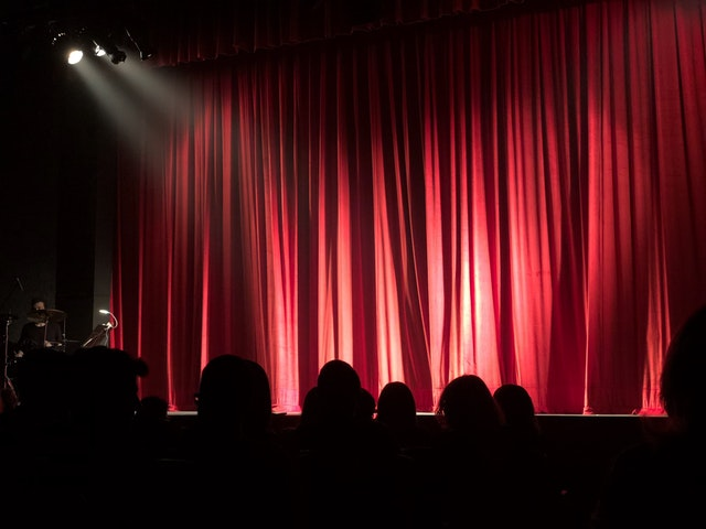 Theater audience looking at red curtain