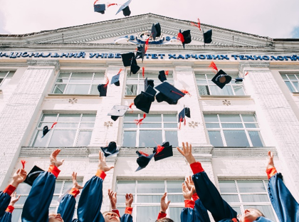 Students in graduation caps and gowns tossing their academic hats in the air.